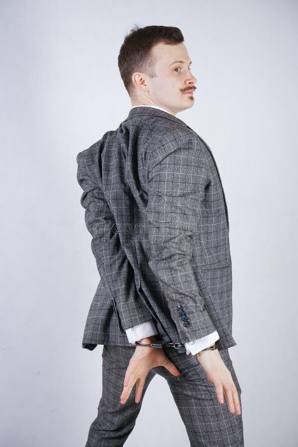 O ladrão caramente vestido sofre da cleptomania e é prendido para um crime um homem em um terno elegante do negócio está em um w imagem de stock