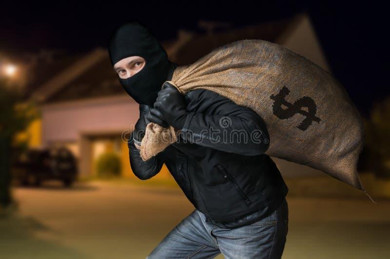 O ladrão corre afastado e está levando o saco completo do dinheiro na noite fotos de stock