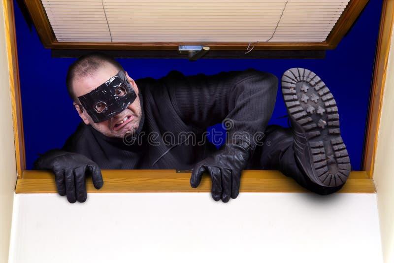 O ladrão escala na casa fotos de stock