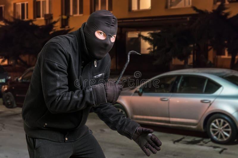 O ladrão mascarado no passa-montanhas com pé de cabra quer roubar um carro fotos de stock royalty free
