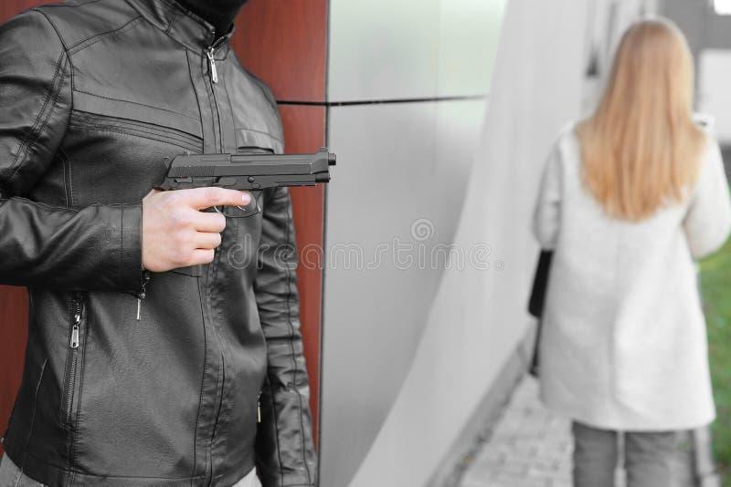 O ladrão masculino com arma está indo roubar fora da mulher imagem de stock royalty free