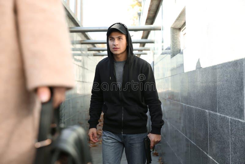 O ladrão masculino com arma está indo roubar fora da mulher imagens de stock