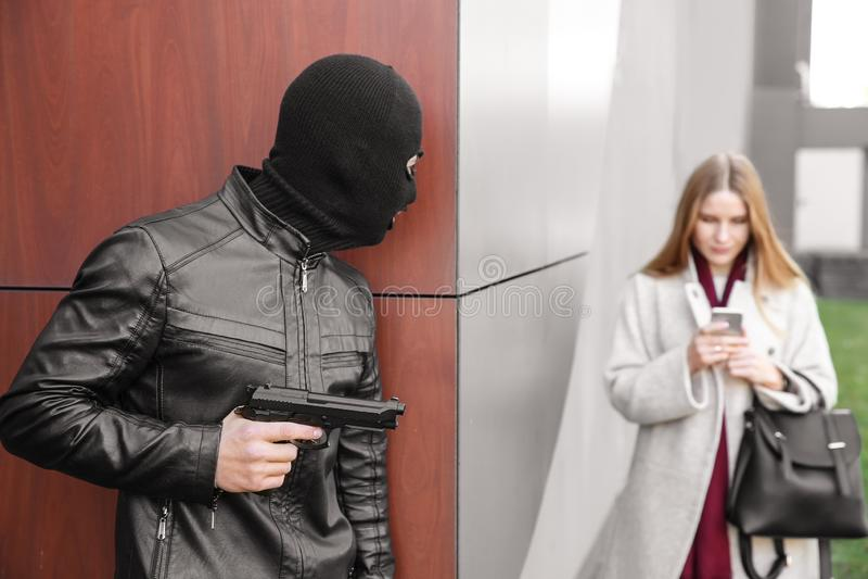 O ladrão masculino com arma está indo roubar fora da mulher imagem de stock