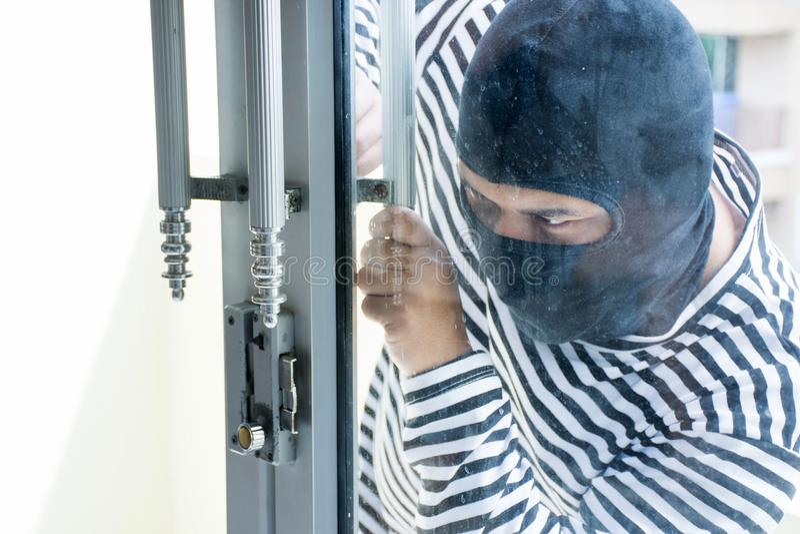O ladrão masculino/invade a tentativa para quebrar na sala roubar foto de stock royalty free