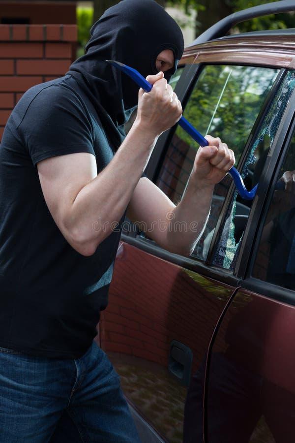 O ladrão quebra a janela de carro imagem de stock royalty free