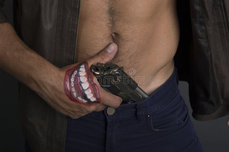 O ladrão retira uma arma dobrou dentro seu brim criminoso e extorsão fotos de stock