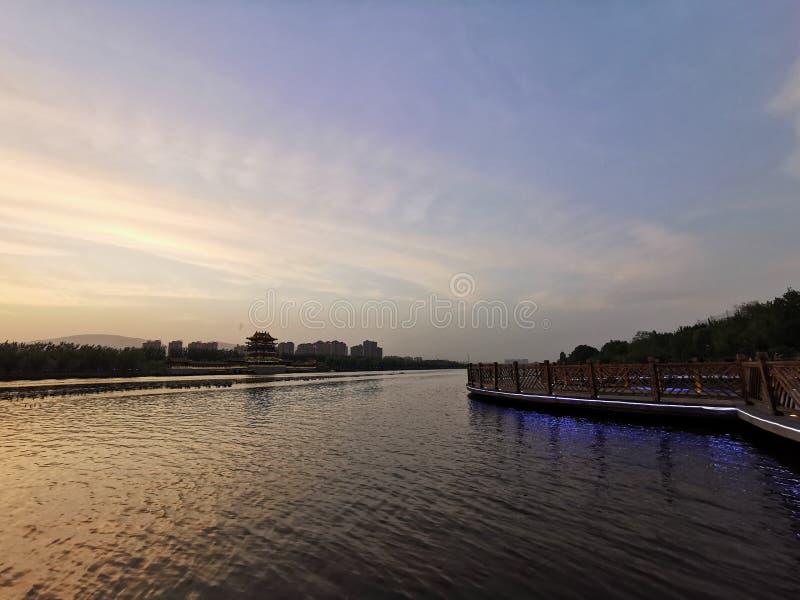 O lago, o céu, o corredor, a construção pequena na distância fotografia de stock royalty free