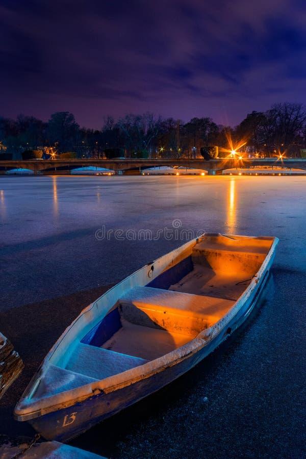 O lago congelado com um barco no inverno disparou durante a noite em uma paridade imagem de stock royalty free
