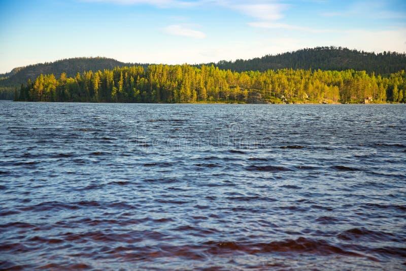 O lago e a floresta suecos pequenos no por do sol iluminam-se na Suécia foto de stock