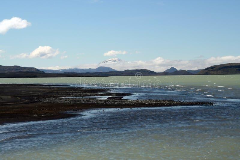 O lago Hálslón com a praia e neve vulcânicas pretas tampou montanhas em Islândia foto de stock
