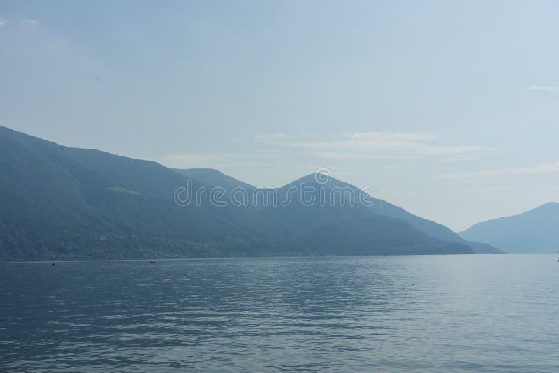 O lago Lago Maggiore com névoa e a montanha ajardinam em Suíça de Ascona fotografia de stock royalty free