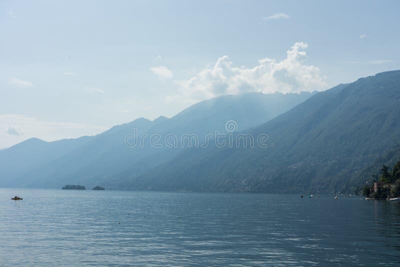 O lago Lago Maggiore com névoa e a montanha ajardinam em Suíça de Ascona fotos de stock