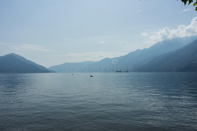 O lago Lago Maggiore com névoa e a montanha ajardinam em Suíça de Ascona imagem de stock royalty free