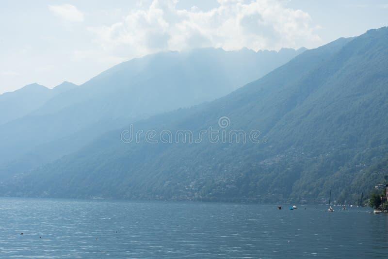 O lago Lago Maggiore com névoa e a montanha ajardinam em Suíça de Ascona fotos de stock royalty free