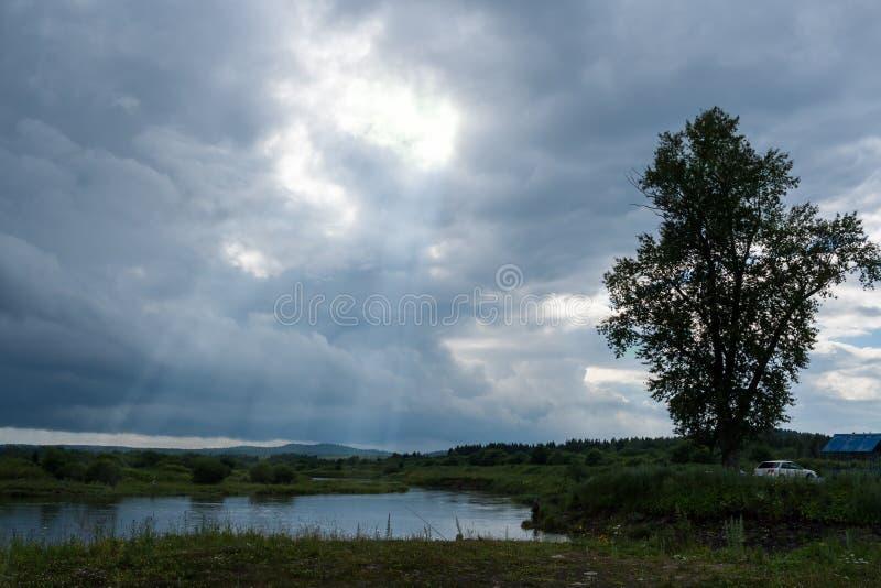 O lago pequeno, os fishermens e o céu nebuloso com sol irradiam imagens de stock royalty free