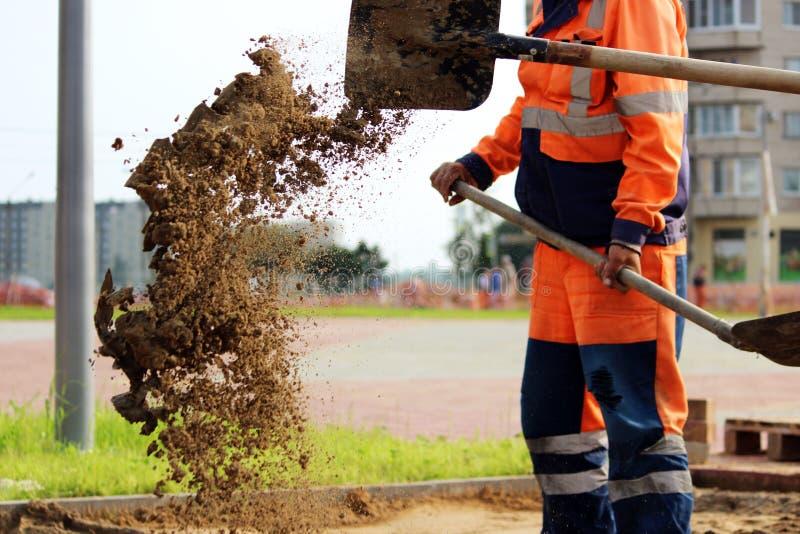 o lance da areia dos pedreiro trabalha com pá colocando pavimentos na praça da cidade foto de stock royalty free