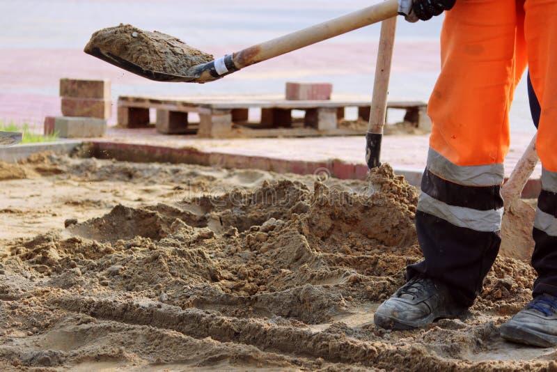 o lance da areia dos pedreiro trabalha com pá colocando pavimentos na praça da cidade fotos de stock royalty free