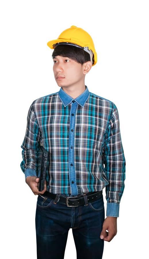 O laptop novo da posse do homem de neg?cios veste o pl?stico amarelo do capacete de seguran?a no conceito branco da constru??o do foto de stock royalty free