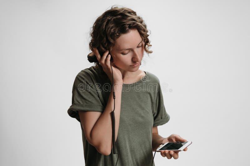 O lazer encaracolado novo da mulher, guarda seus fones de ouvido estereof?nicos modernos fotografia de stock royalty free
