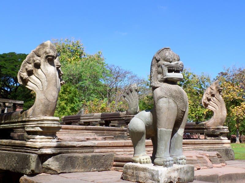 O leão e sete dirigiram as esculturas sob o céu azul vívido, a entrada do Naga do parque histórico de Phimai em Nakhon Ratchasima imagem de stock