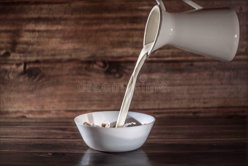 O leite derrama dentro a placa branca com cereais fotos de stock royalty free