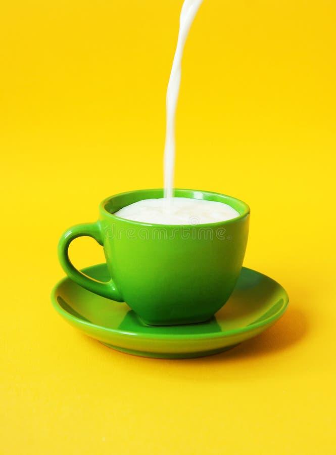 O leite derrama dentro um copo verde O conceito de comer saudável, bebida da dieta fotos de stock