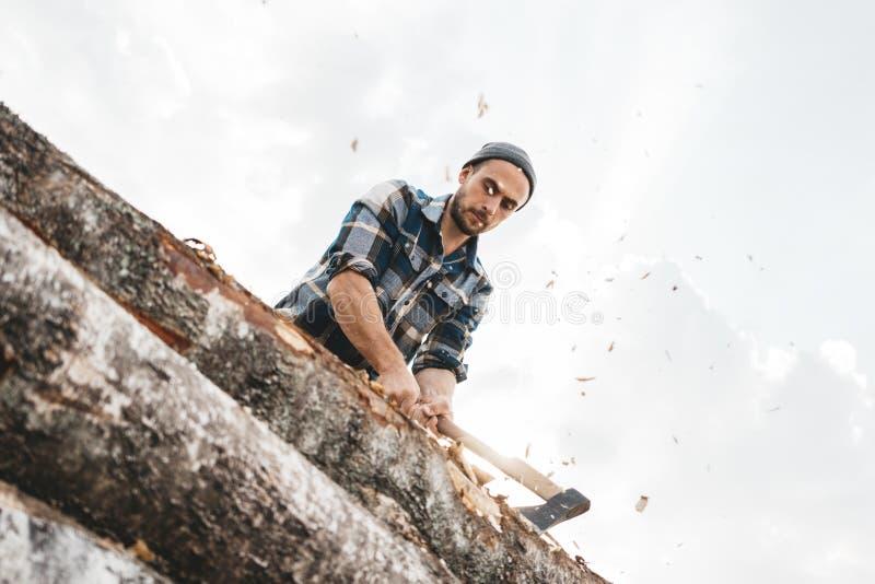 O lenhador brutal corta a floresta com machado afiado imagem de stock royalty free