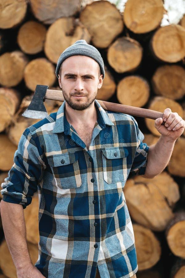 O lenhador farpado forte guarda o machado em seu ombro imagem de stock royalty free