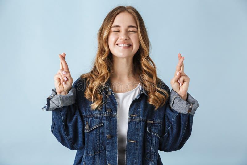O levantamento bonito novo bonito da mulher isolado sobre o fundo azul da parede para fazer por favor os dedos esperançosos do ge fotos de stock