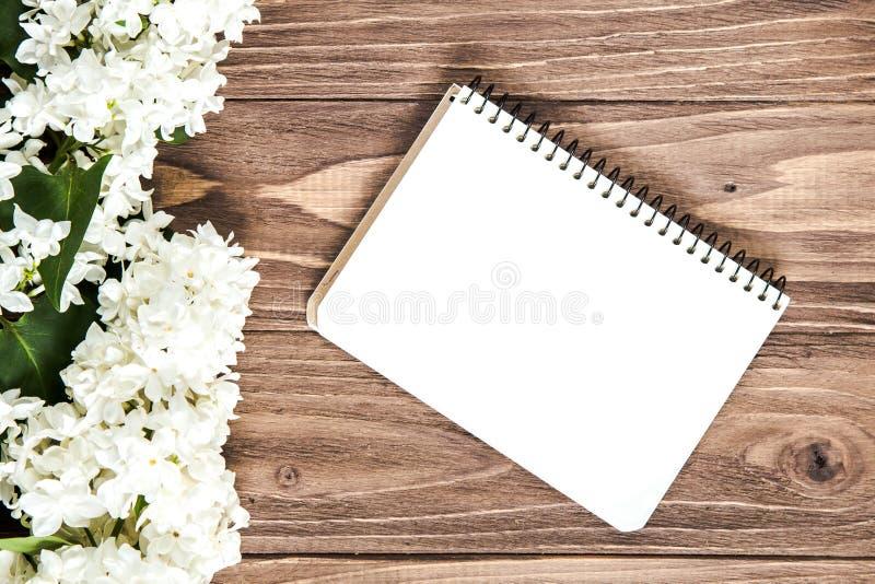O lilás branco floresce a composição na tabela de madeira com um caderno vazio para desejos e cumprimentos imagem de stock royalty free