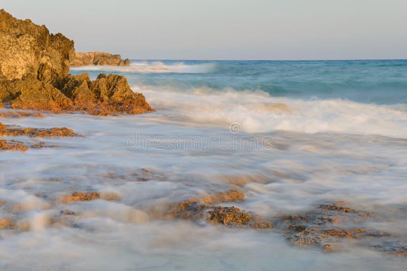 O litoral com ondas e penhascos desvaneceu-se no por do sol imagens de stock
