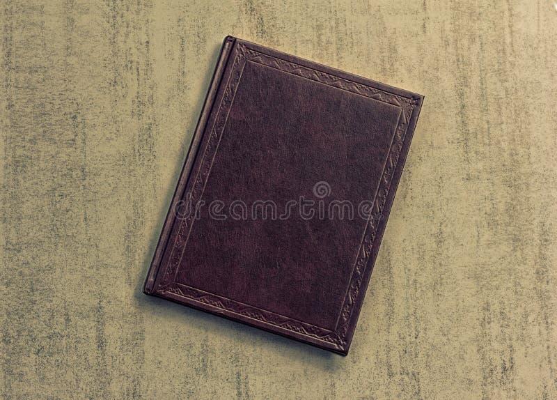 O livro é roxo escuro em um fundo cinzento do grunge, vista superior fotos de stock