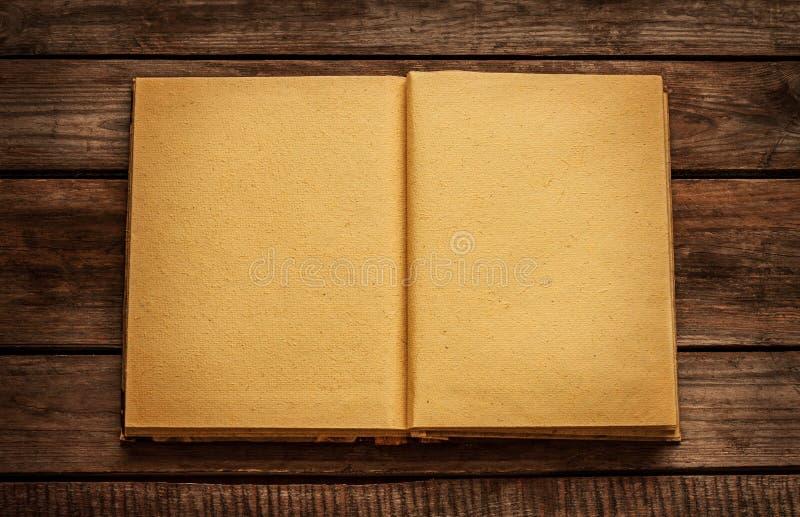 O livro aberto da placa velha no vintage planked a tabela de madeira foto de stock