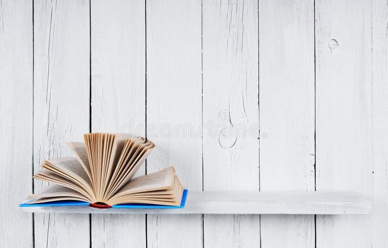O livro aberto em uma prateleira de madeira fotografia de stock royalty free