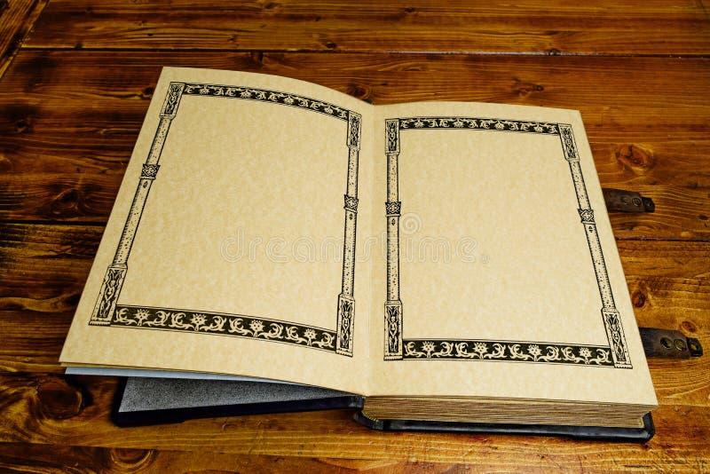 O livro aberto nas páginas dos primeiros, estabelece à tabela de madeira marrom escura imagem de stock