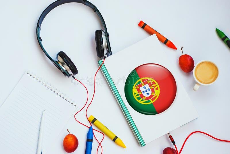 O livro com bandeira e os fones de ouvido portugueses fotografia de stock