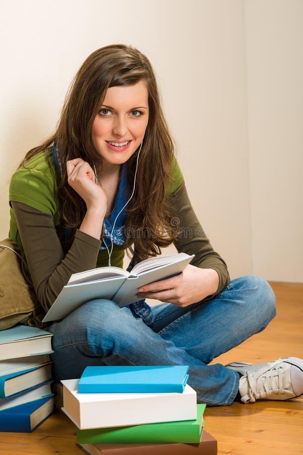 O livro da preensão da mulher do adolescente do estudante escuta música imagens de stock royalty free