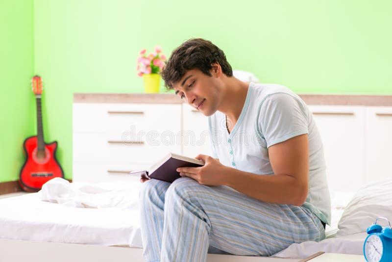 O livro de leitura considerável novo do estudante na cama fotografia de stock royalty free