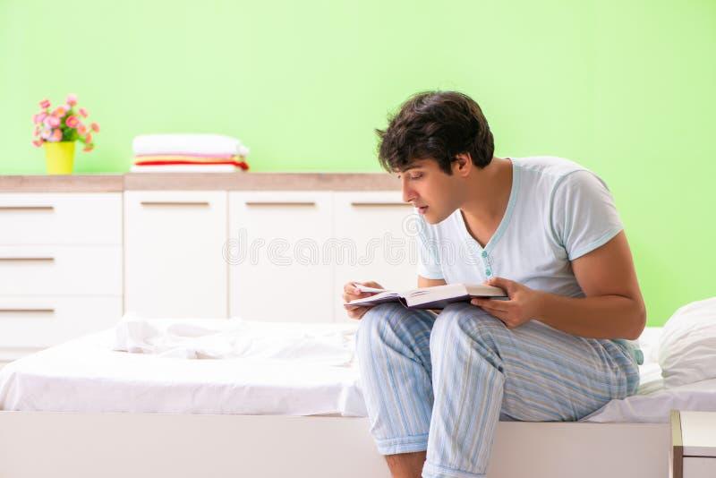 O livro de leitura considerável novo do estudante na cama imagem de stock royalty free