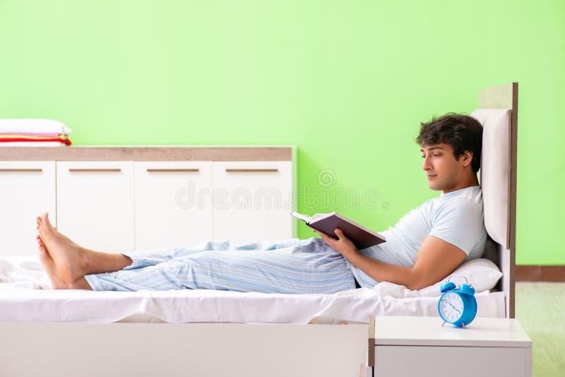 O livro de leitura considerável novo do estudante na cama imagens de stock royalty free