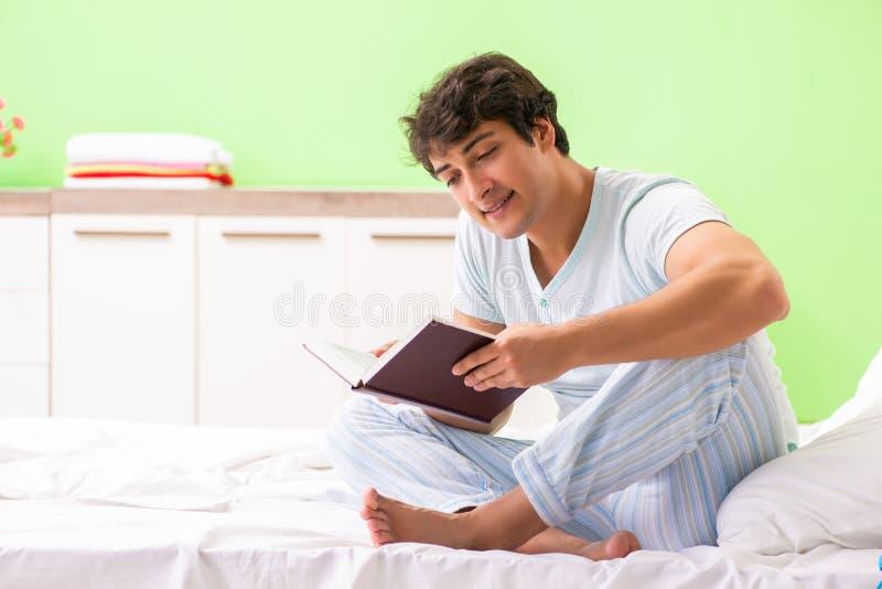 O livro de leitura considerável novo do estudante na cama foto de stock royalty free