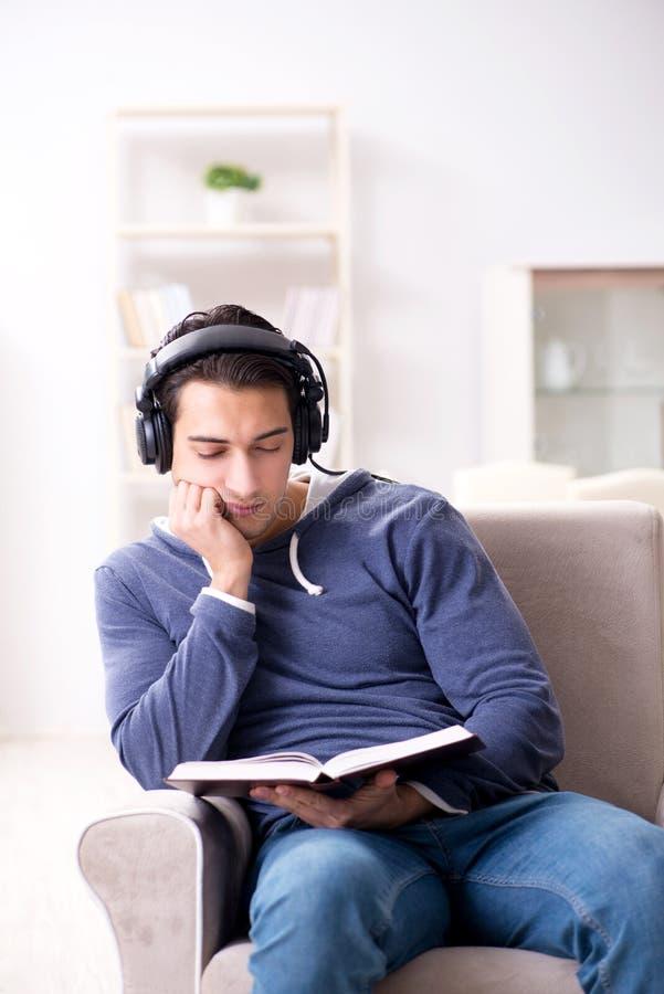 O livro de leitura do homem novo e escuta o livro audio foto de stock