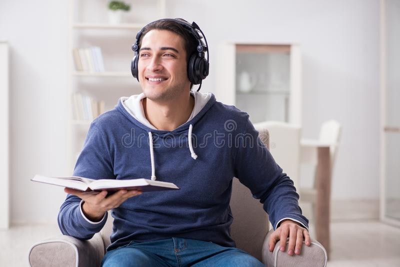 O livro de leitura do homem novo e escuta o livro audio fotografia de stock