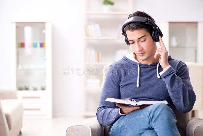 O livro de leitura do homem novo e escuta o livro audio fotografia de stock royalty free