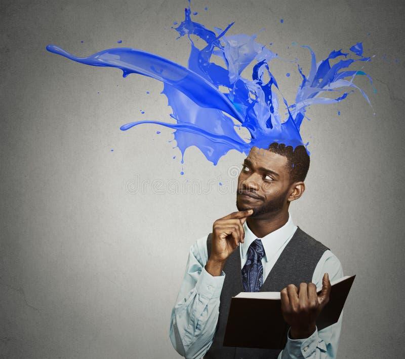 O livro de leitura pensativo do homem de negócios colorido espirra a saída da cabeça imagens de stock royalty free