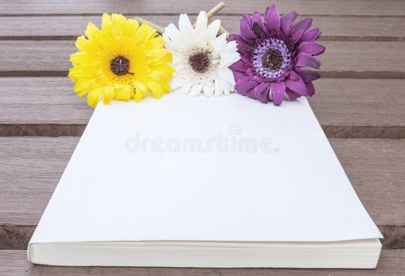 O livro de nota branco do close up com a flor falsificada colorida na tabela de madeira velha borrada textured o fundo imagens de stock royalty free