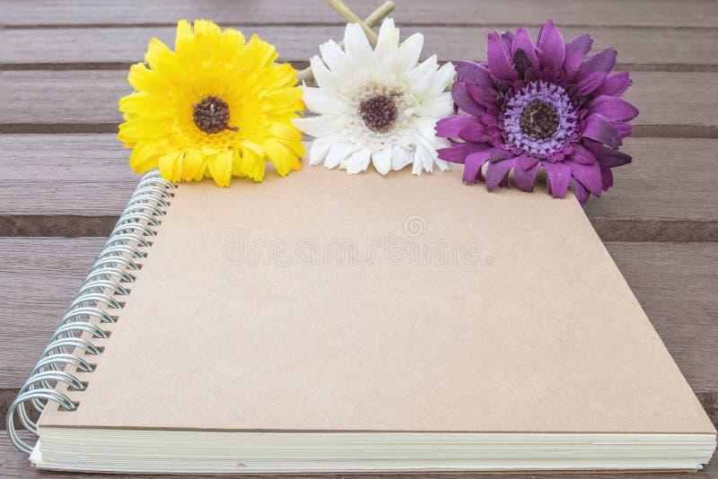 O livro de nota marrom do close up com a flor falsificada colorida na tabela de madeira velha borrada textured o fundo fotos de stock