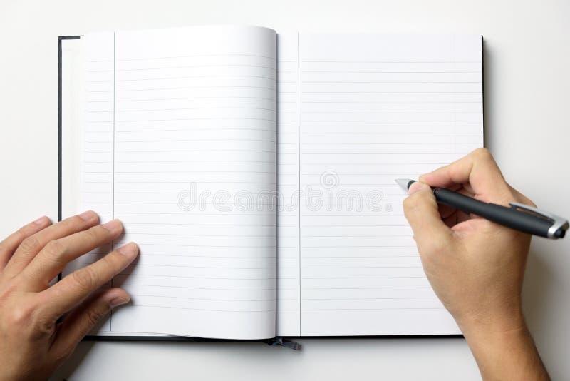 O livro de nota vazio com mãos do homem guarda uma pena foto de stock
