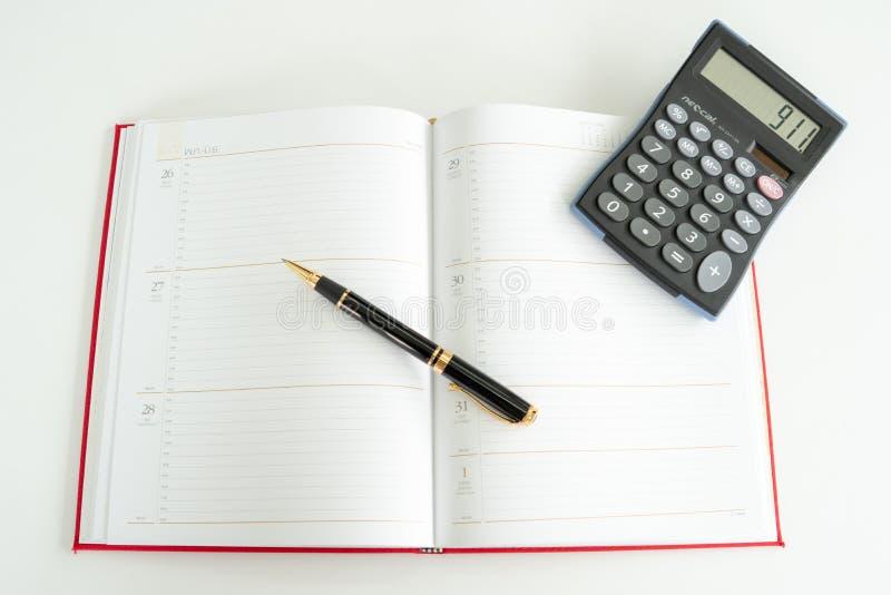 O livro diário do plano espalhou para fora com uma pena e uma calculadora de fonte nele fotografia de stock