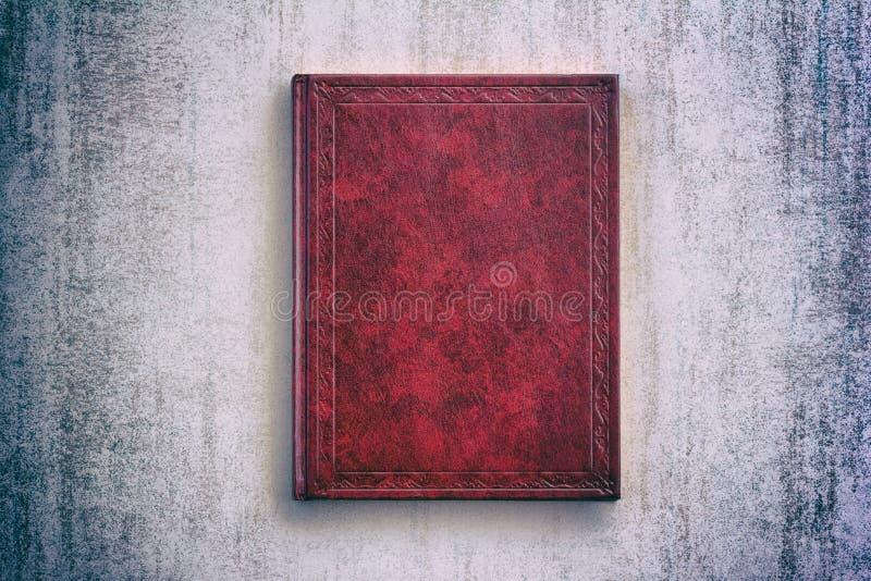 O livro em uma tampa vermelha sobre o fundo cinzento do grunge, vista superior foto de stock royalty free